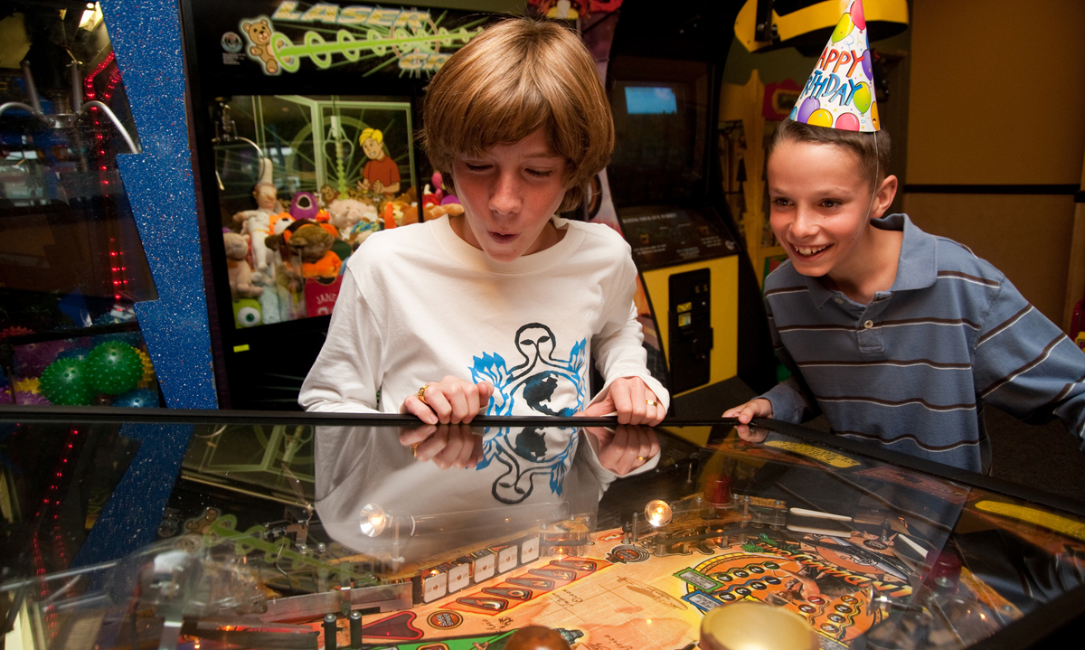 Kids having fun playing pinball at Straw Hat Pizza