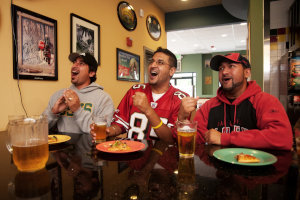 Three guys with beer and pizza watching an exciting sports game on the restaurant's big screen