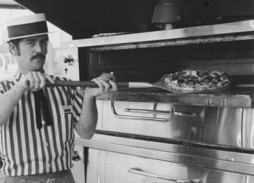 Old-tyme cook taking a pizza out of the oven