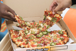 Two customers grab slices from a large, delicious pizza
