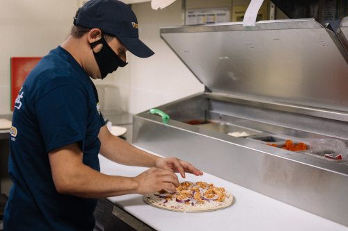 A pizza maker preps a pizza while wearing a mask